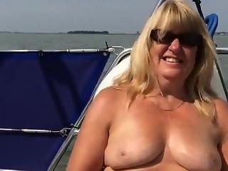 Big titted mature masturbating on a boat.